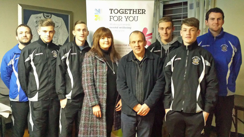 "Andrea Warwick, Employment Officer at Action Mental Health in Derriaghy joins members of Lisburn Distillery Football Club as they benefit from one of their MenSsana ""Provoking Thought"" workshops for young people, part of the Together For You project, funded by the Big Lottery Fund."