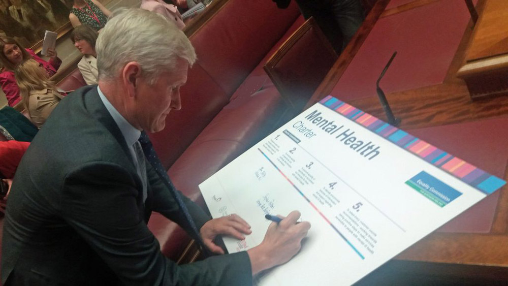 David Babington, Chief Executive of AMH, signs the Mental Health Charter
